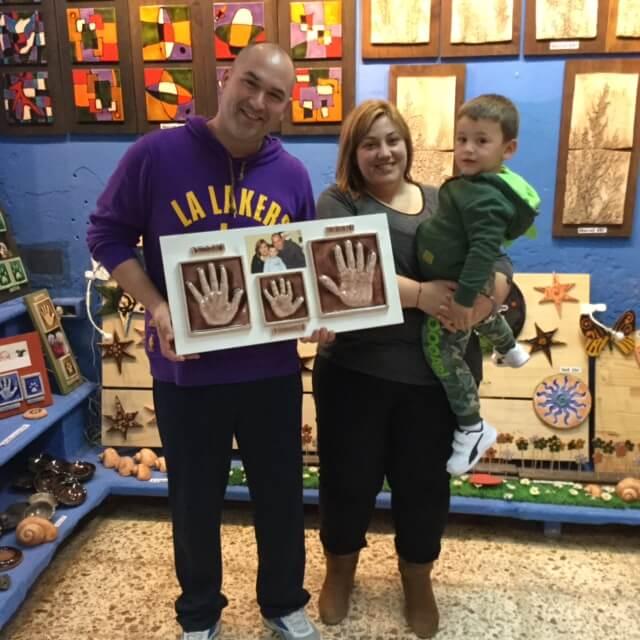 familia contenta con sus huellas cerámicas en tienda huelladebebes